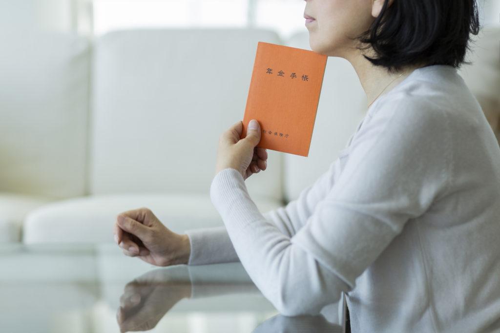 年金生活者支援給付金制度とは-年金手帳を持つ女性