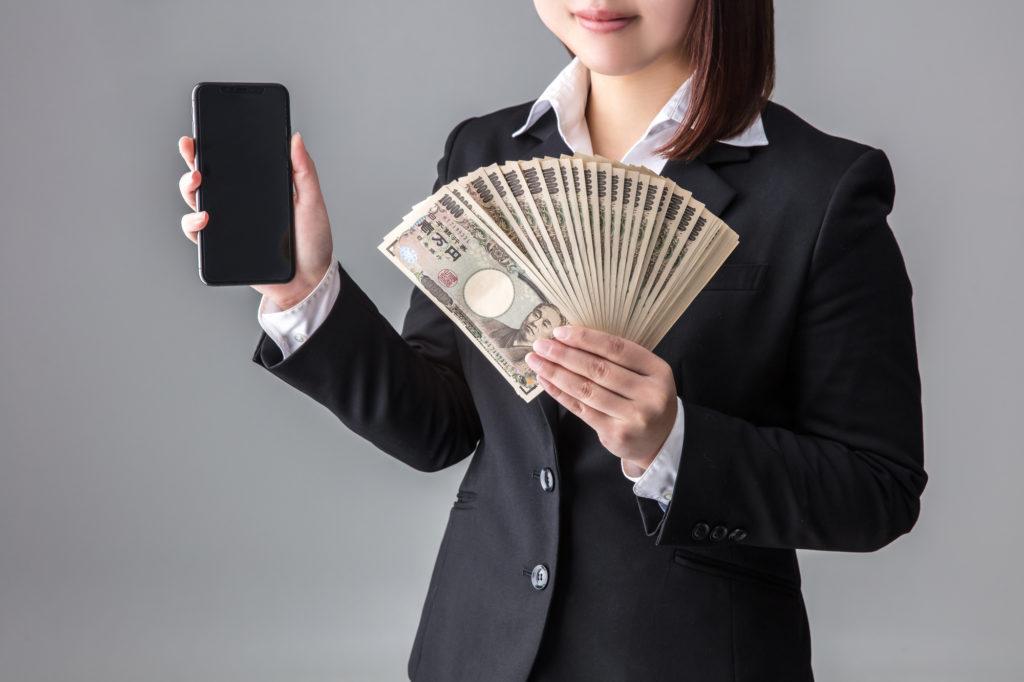 携帯とお金を持つスーツの女性