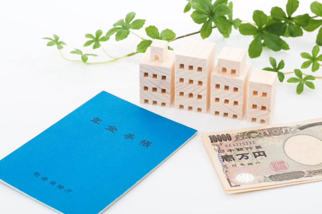年金担保貸付審査-年金手帳と現金と家の置物