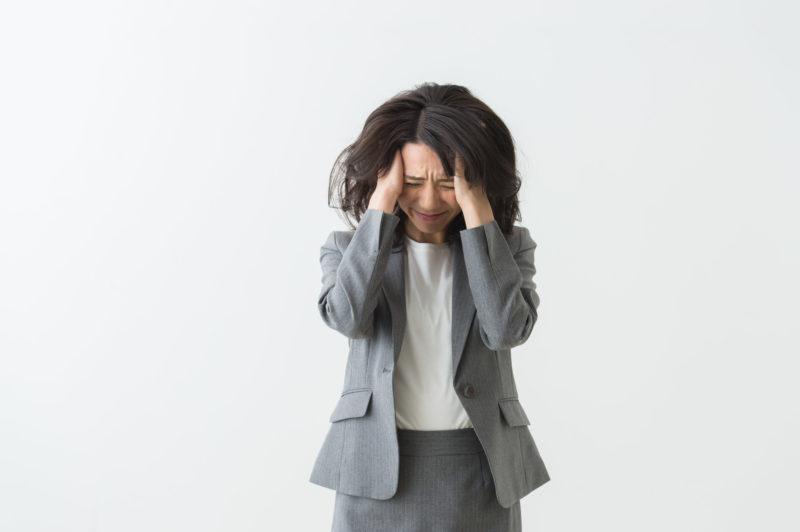 カードローン 返済額 減らす-頭を抱える女性