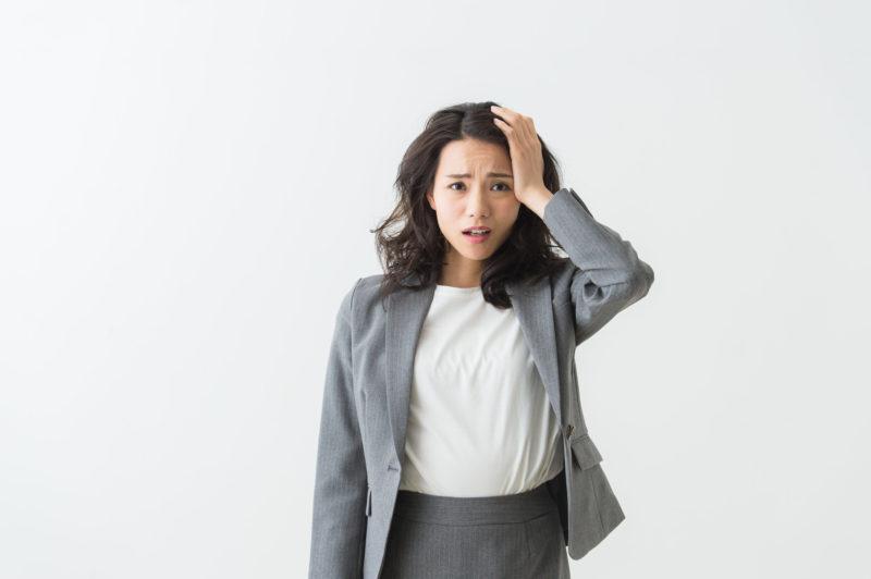 片手で髪の毛を抑える女性