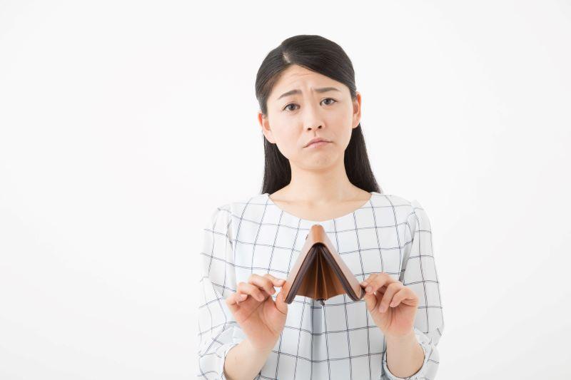 空っぽ財布を持っている女性