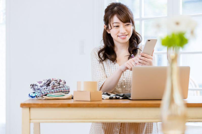 服とパソコンとスマホで検索している女性